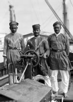Three Lascars of the 'Viceroy of India' (1929), standing behind the wheel of one of the ship's tenders.
